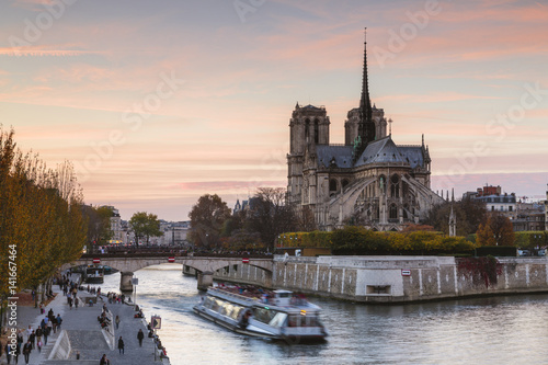 Boat on Seine River by Notre Dame de Paris against sky during sunset