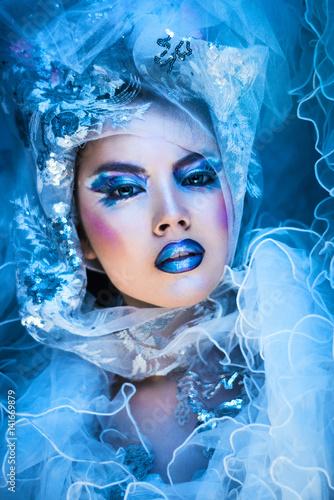 Aluminium Prints Painterly Inspiration Winter beauty woman. Fashion portrait over blue snow Background.