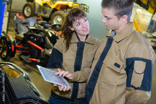 Young mechanics looking at screen of tablet