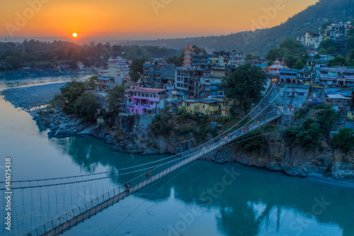 View of River Ganga and Lakshman Jhula bridge at sunset with a blue sky and colorful houses Canvas Print