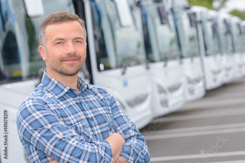 Portrait of man with fleet of buses Canvas Print