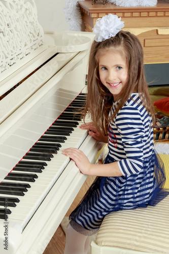 Foto op Canvas Muziekwinkel Girl smiling sitting behind the keys of a large white piano.