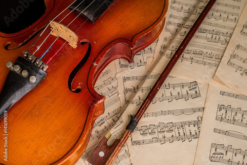 Old violin lying on the sheet of music - Buy this stock