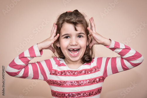 Toothless young girl gesticulating and making a face Poster