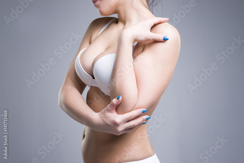 Fototapeta Woman in white push up bra on gray background, perfect female breast