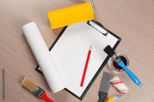 Fotografia, Obraz  Clipboard and decorator instruments on wooden table
