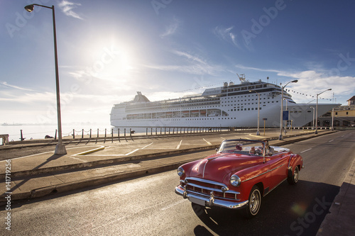 Poster Havana Old car on street of Havana at sunrise with cruise ship in background, Cuba