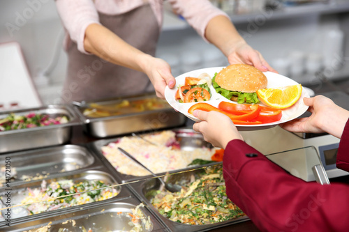 Fotografie, Tablou Pleasant woman giving lunch to school girl in cafeteria