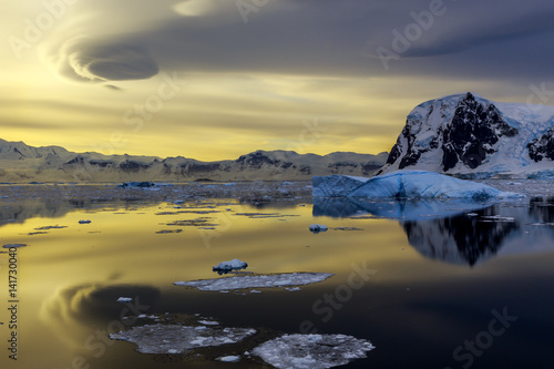 Photo Stands Antarctic Blue iceberg, mountains and sunset reflecting in ocean at Lemaire Strait, Antarctica
