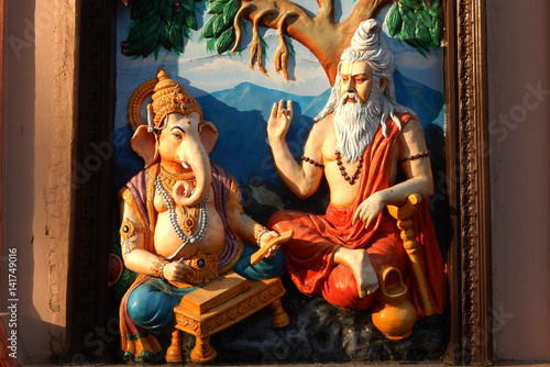 Wall art of Sage Vyasa dictating the story to help God Ganesha to write Hindu epic in temple