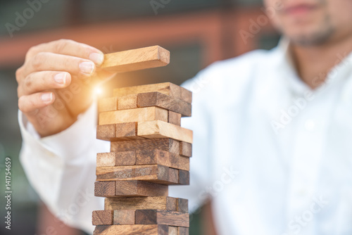 Fotografía  Closeup of businessman making a pyramid with empty wooden cubes