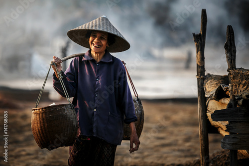 Fotografie, Obraz  Woman working on salt field in Thailand, Boiling rock salt, crystallized salt fr