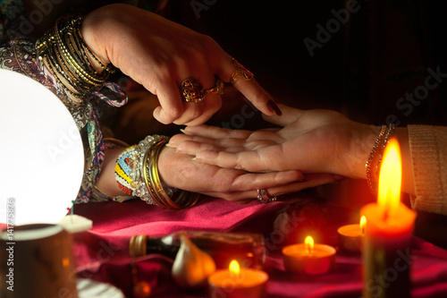 Gypsy woman reading future from another womans palm