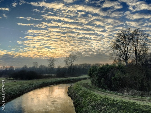 Sunset cloudy sky reflected in the river Canvas Print