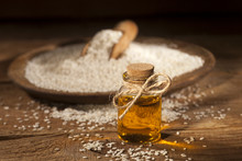 Fresh Sesame Oil In A Glass Bottle And Seeds In Wooden Plate And Spoon