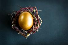 Golden Easter Egg In The Nest On Dark Background