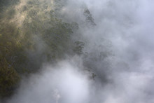 The Mist Rising From The Bottom Of Kalalau Valley Envelopes The Tropical Vegetation In Kauai.