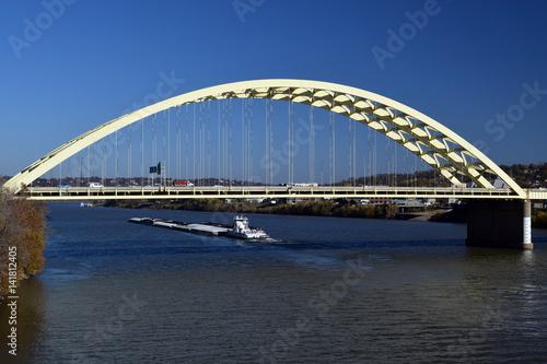 boat on the ohio river passing under the big mac bridge in