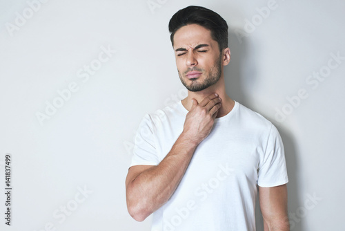 Fotomural Young man having sore throat and touching his neck, wearing a loose white t-shirt against light grey background