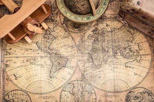 drewniany-samolot-i-stara-walizka-na-tle-map