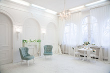 Classical White Interior Room With Turquoise Chairs, Vintage Style Chandelier, Fireplace, Big Window And Spring Flowers In Vase On Table. Horizontal