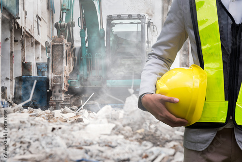 Engineer or Safety officer holding hard hat with the heavy equipment excavator demolition demolish machine in construction site Canvas Print