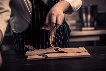 Chef cutting the fish on a board