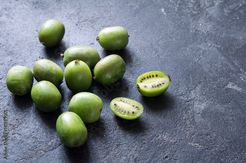 Baby kiwi or mini kiwi fruits on stone background. Closeup view Canvas Print