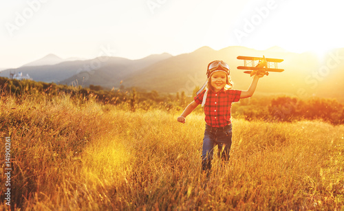 Fototapety, obrazy: Child pilot aviator with airplane dreams of traveling in summer  at sunset.