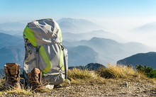 Hiking Equipment. Backpack And Boots On Top Of Mountain.