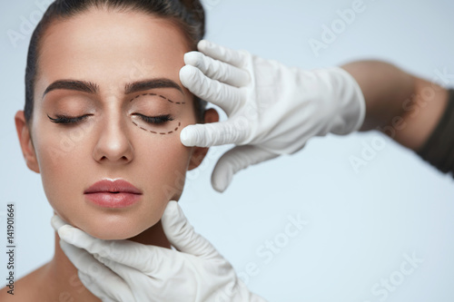 Obraz Closeup Of Beautician Hands Touching Young Female Patient Face - fototapety do salonu