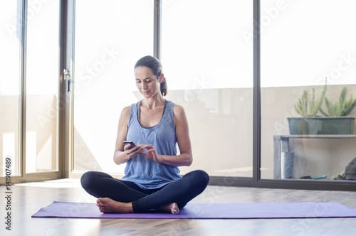 Woman using smart phone while sitting on exercise mat at home