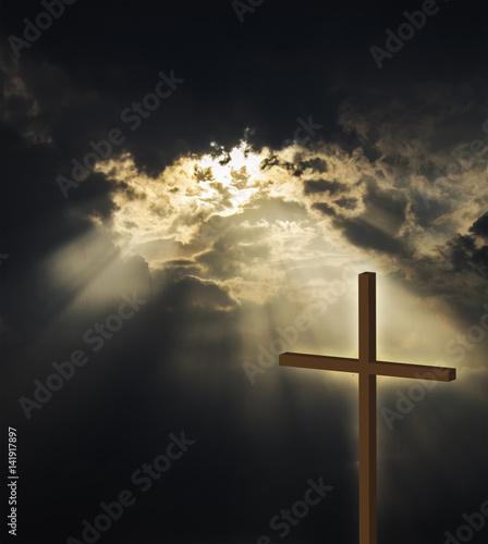 Photographie Raggi di luce che filtrano dal cielo e illuminano la croce