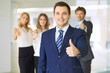 Successful young business people showing thumbs up sign while standing in office interier