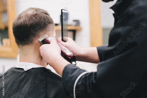 Barber cuts the client mac Haircut men Barbershop. Men's Hairdressers; barbers.