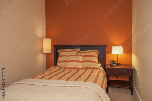 small space modern bedroom orange walls and striped sheets ...