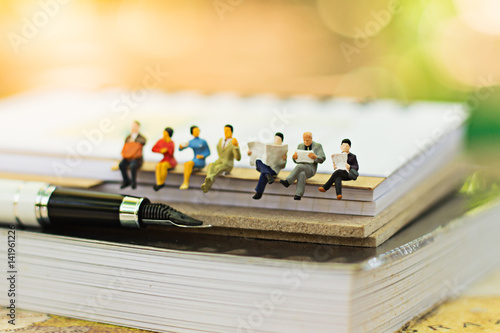 Fotografie, Obraz  Miniature people sitting on book using as background education or business conce