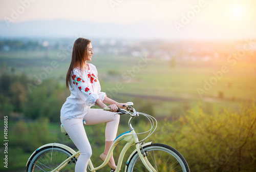 Woman with retro bike on the hill in the evening Canvas Print