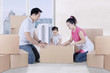 Young parents packing cardboard with their daughter