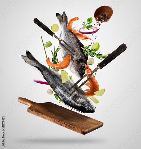 Poster Fish Flying raw whole bream fish and prawns with ingredients