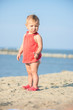 Baby playing on the sandy beach near the sea. Cute little girl in red dress with sand on tropical beach. Ocean coast.