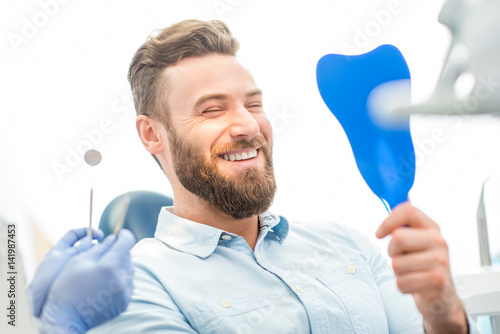 Fotografía  Handsome male patient looking at his beautiful smile sitting at the dental offic