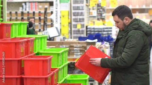 20s people buy red box in male. Youth adult boy in store. House hold goods. Guy chooses a box to buy. The buyer holds the object in hand. Male in mall 4k. Preparation for relocation.