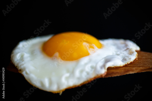 Deurstickers Gebakken Eieren Fried egg with a wooden spoon