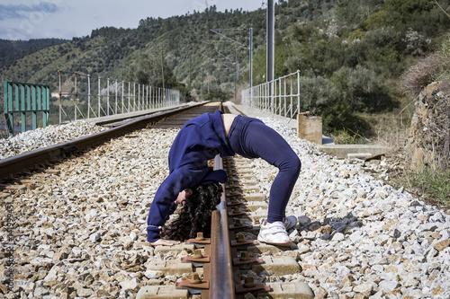 Tuinposter Gymnastiek Haciendo gimnasia en las vías del tren. Niña jugando feliz en las vías del tren.