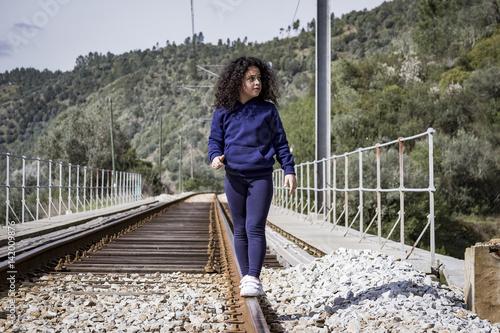 Fotografia, Obraz  Niña jugando feliz en las vías del tren.