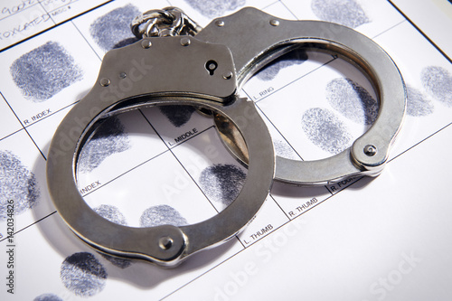 Photo Handcuffs laying on top of fingerprint chart
