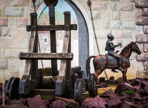 Obraz na płótnie Photo of a rider in medieval armor against a catapult