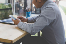 Businessman Hand Holding A Credit Card Intent To Made A Online Payment With Smartphone On His Desk.