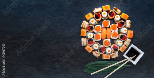 Foto  Sushi net on a black surface. Flat lay